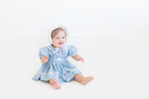 baby girl at 10 months old in blue vintage baby girl dress and a beautiful vintage bonnet in natural light studio in Cross Plains, Tennessee. Photo taken by Melanie Grady of Bump and Bonnet - Nashville's premier child photographer