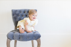 baby girl at 10 months old in yellow vintage baby girl dress and a beautiful vintage blue chair in natural light studio in Cross Plains, Tennessee. Photo taken by Melanie Grady of Bump and Bonnet - Nashville's premier child photographer