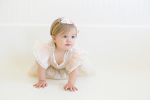baby girl at 10 months old in creamy vintage baby girl dress and a beautiful vintage inspired headband in natural light studio in Cross Plains, Tennessee. Photo taken by Melanie Grady of Bump and Bonnet - Nashville's premier child photographer